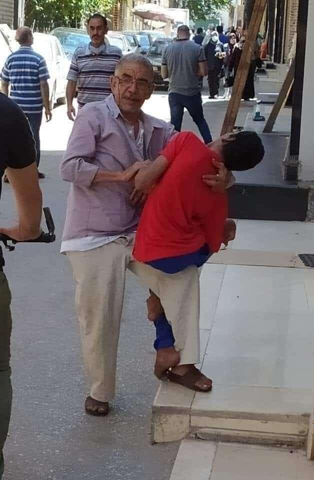 يجوب الشوارع حاملاً ابنه علي كتفه.. رجل يستغيث لعلاج ابنه